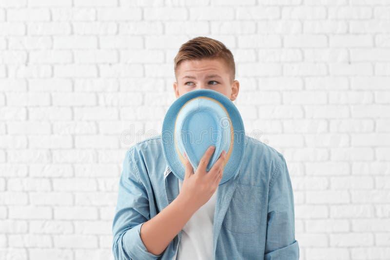 Портрет красивой стороны заволакивания молодого человека со шляпой против белой кирпичной стены стоковое изображение