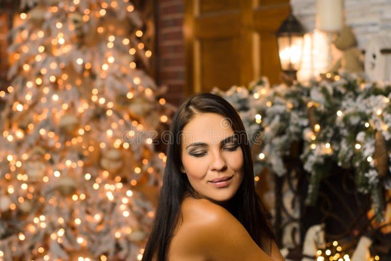 Портрет красивой счастливой темноволосой женщины в новогоднем интерьере, ожидающей рождественских праздников, вечерней фотографии стоковая фотография rf