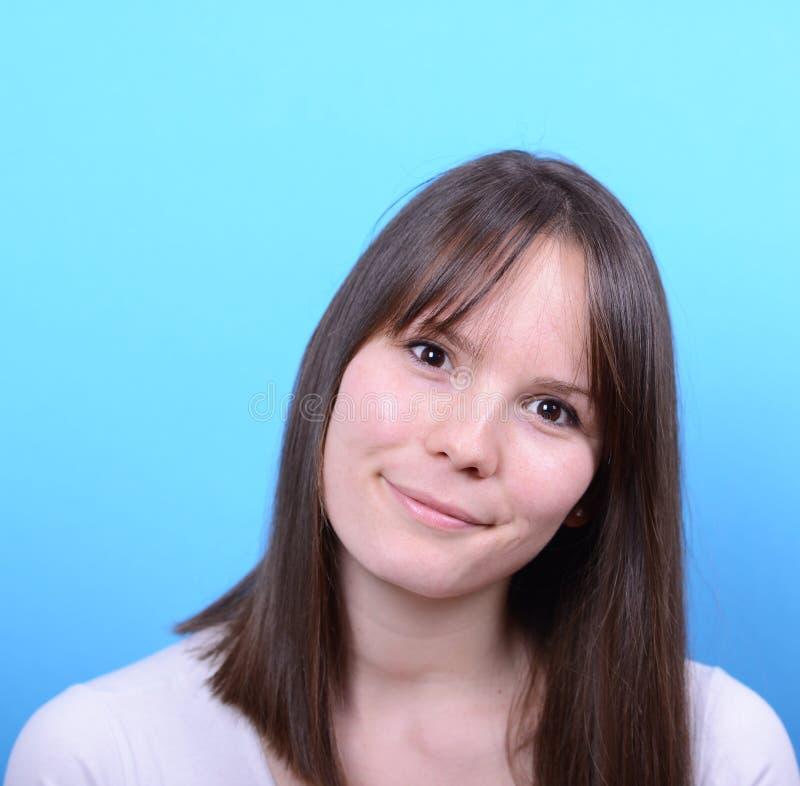 Портрет красивой счастливой женщины против голубой предпосылки стоковое изображение