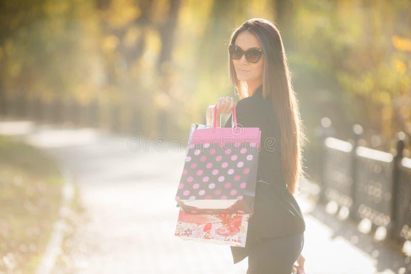 Портрет красивой счастливой женщины стоя на улице держа усмехаться хозяйственных сумок стоковое изображение