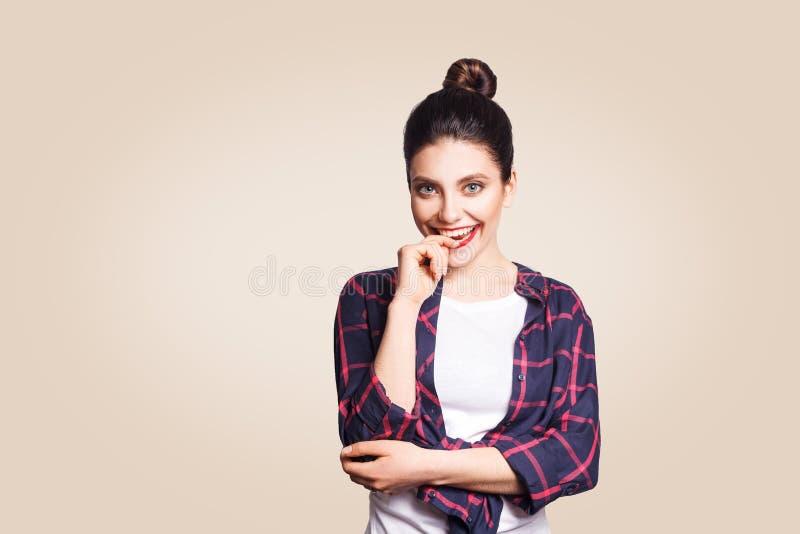 Портрет красивой счастливой зубастой девушки smiley в непринужденном стиле смотря камеру и toching ее губы и зубы с пальцем стоковое фото