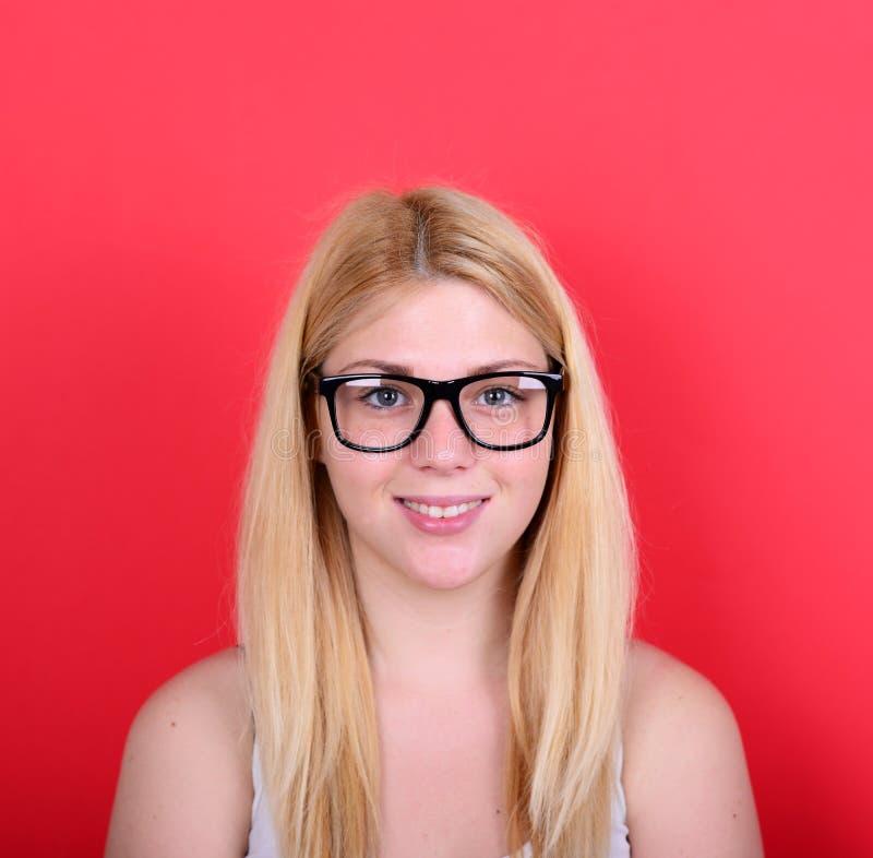 Портрет красивой счастливой молодой женщины против красной предпосылки стоковые изображения