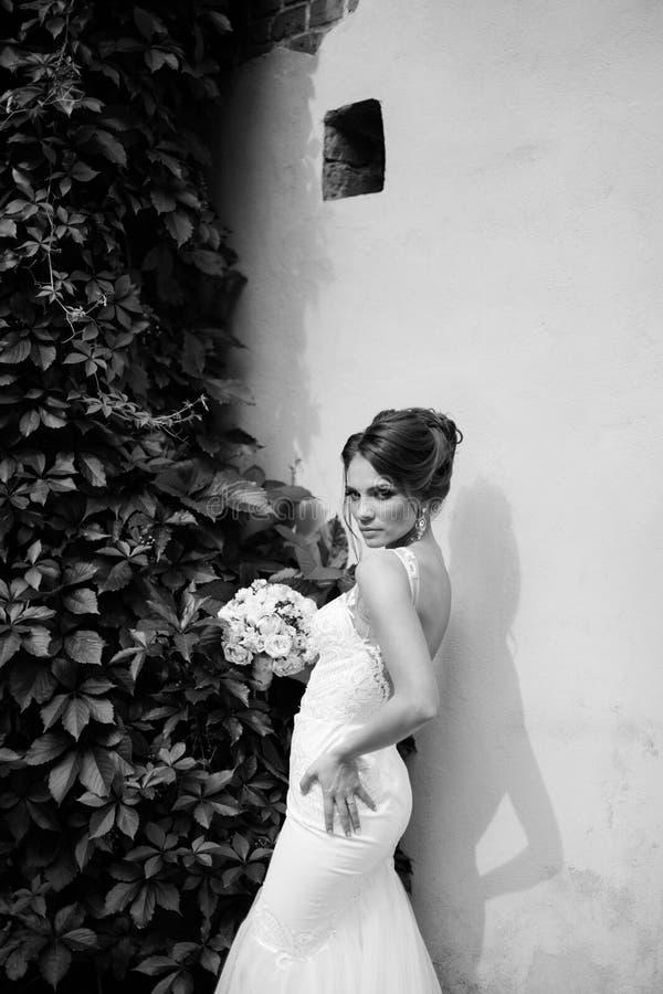 Портрет красивой счастливой невесты брюнет в wedding белом платье держа руки в букете цветков outdoors стоковые фото