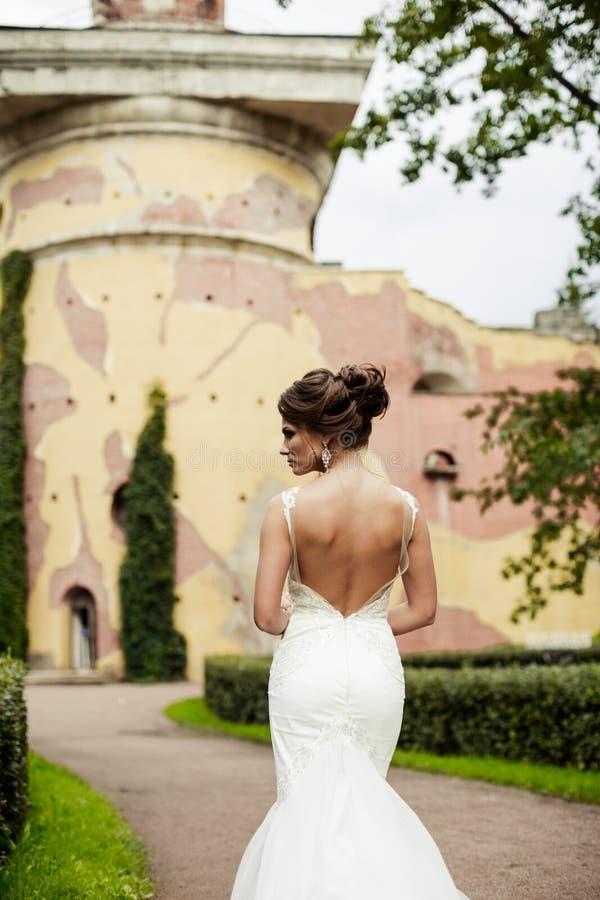 Портрет красивой счастливой невесты брюнет в wedding белом платье держа руки в букете цветков outdoors стоковая фотография