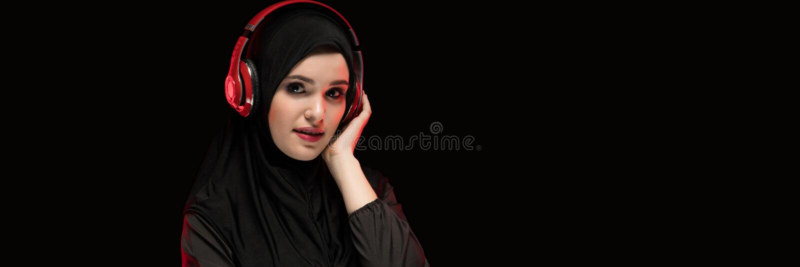 Портрет красивой умной молодой мусульманской женщины нося черное hijab слушая к музыке в наушниках с copyspace дальше стоковое фото rf