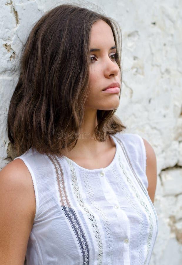 Портрет красивой унылой девушки в белом платье стоковое фото