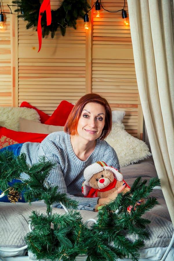Портрет красивой усмехаясь женщины кладя в спальню, со светами рождества и украшениями стоковое изображение rf
