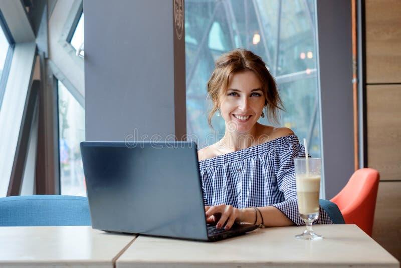Портрет красивой усмехаясь женщины сидя в кафе с черной компьтер-книжкой стоковое фото