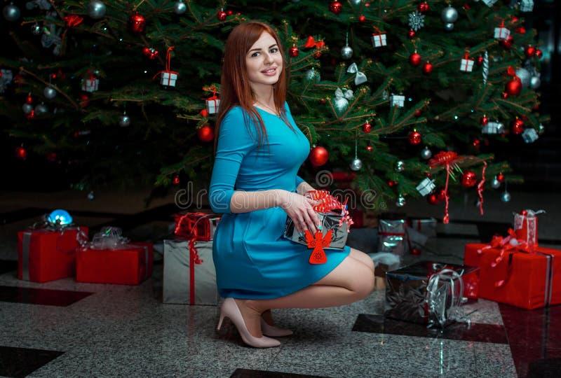 Портрет красивой усмехаясь молодой женщины, представляющ около рождественской елки, держа подарок стоковые изображения rf