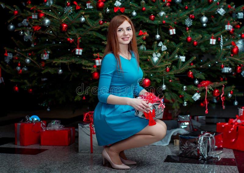 Портрет красивой усмехаясь молодой женщины, стоящ около рождественской елки, держа подарок стоковые изображения rf