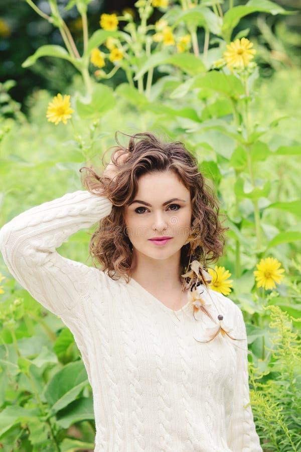 Портрет красивой усмехаясь молодой белой кавказской женщины девушки касаясь ее волосам темного коричневого цвета, в белом свитере стоковое фото rf
