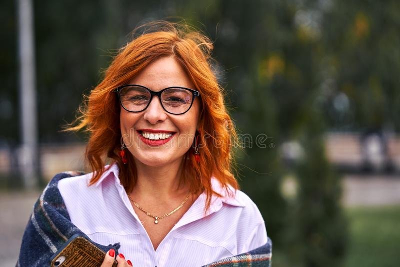 Портрет красивой усмехаясь средн-достигшей возраста женщины со стеклами красных волос нося на пасмурный день стоковые изображения rf