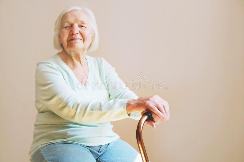 Портрет красивой усмехаясь старшей женщины с идя тросточкой на светлой предпосылке дома стоковое изображение rf