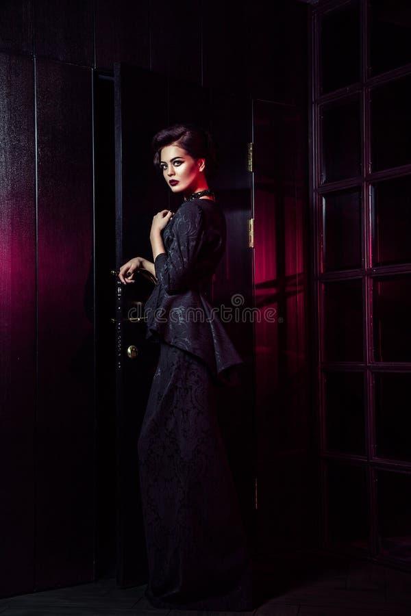 Портрет красивой фотомодели в классическом черном платье, составе и стиле причёсок около темных положения и представлять двери стоковое фото rf
