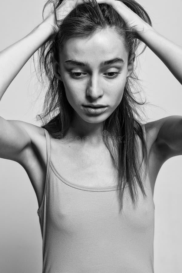 Портрет красивой фотомодели представляя над серой предпосылкой стоковое изображение