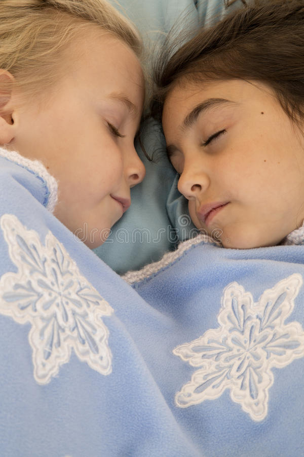 Портрет 2 красивых маленьких девочек уснувших в кровати стоковые изображения