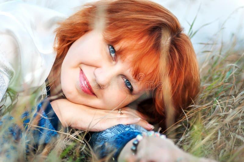 Портрет красной девушки волос лежа на траве летом стоковые изображения rf