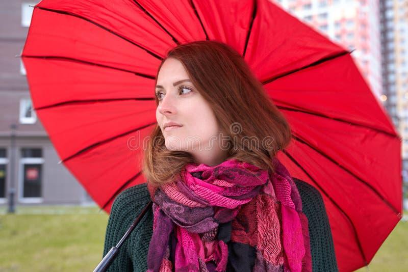 Портрет красной длинн-с волосами молодой женщины идя через stre стоковые изображения rf