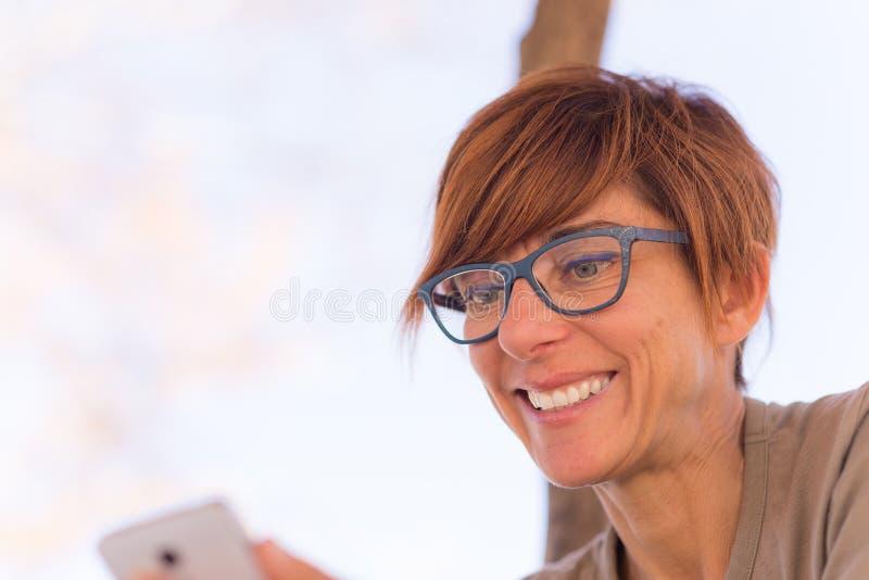 Портрет красной с волосами женщины с зелеными глазами и жизнерадостным выражением лица, усмехаясь пока смотрящ smartphone в руках стоковые изображения rf