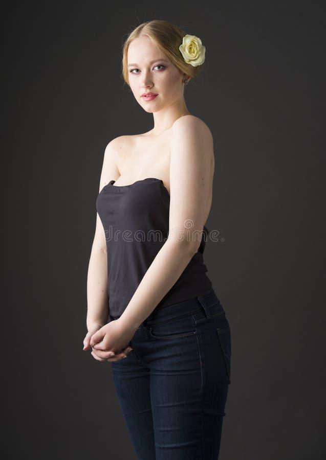 Портрет красоты детеныша плюс блондинка размера с розой желтого цвета в ее волосах стоковое изображение
