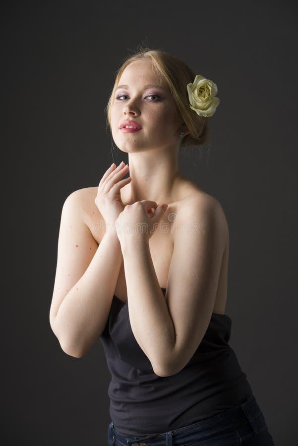 Портрет красоты детеныша плюс блондинка размера с розой желтого цвета в ее волосах стоковая фотография rf