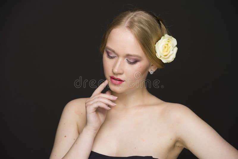 Портрет красоты молодой блондинкы с розой желтого цвета в ее волосах стоковое фото rf