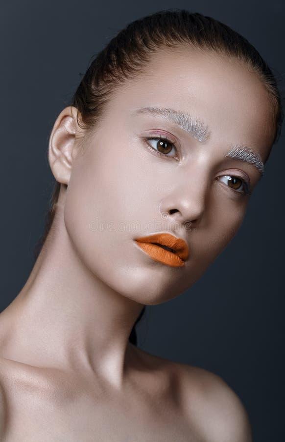Портрет красоты молодых женщин/девушки с оранжевой губной помадой, белым e стоковое фото