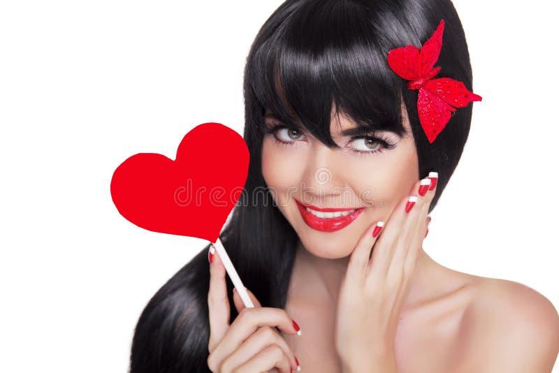 Портрет красоты счастливой усмехаясь девушки при красные губы держа красный цвет стоковое изображение rf