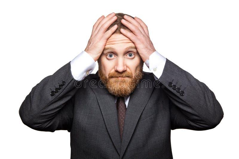 Портрет крупного плана грустного красивого бизнесмена с лицевой бородой в черном положении костюма держа его голову и смотря каме стоковые изображения rf