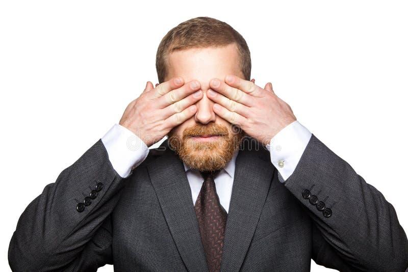 Портрет крупного плана красивого бизнесмена с лицевой бородой в черном положении костюма и закрыл его глаза и не хочет к смотреть стоковые фото
