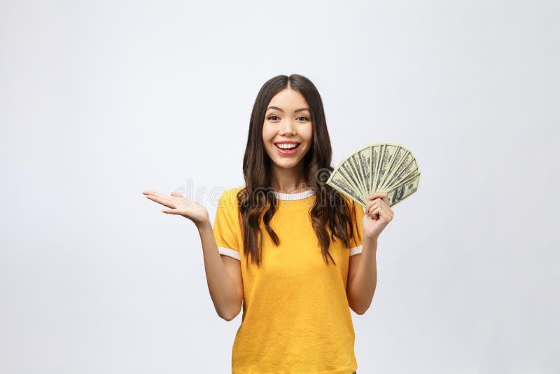 Портрет крупного плана красивой азиатской женщины держа деньги изолированный на белой предпосылке Азиатская девушка считая ее зар стоковые фото