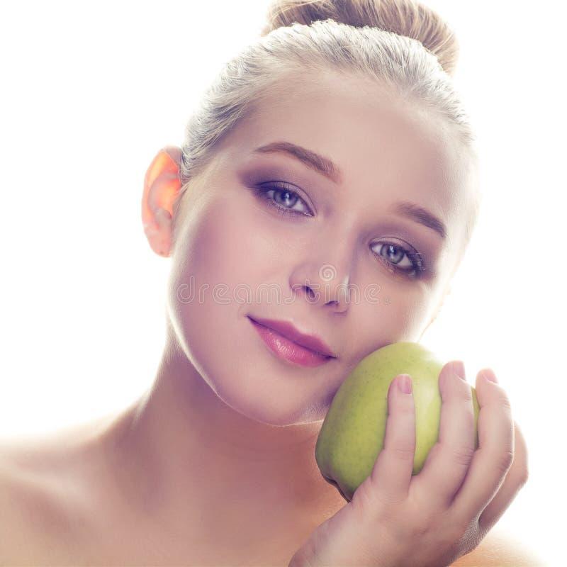 Портрет крупного плана красивой белокурой девушки при состав держа зеленое яблоко рядом с ее щекой против белой предпосылки стоковые изображения