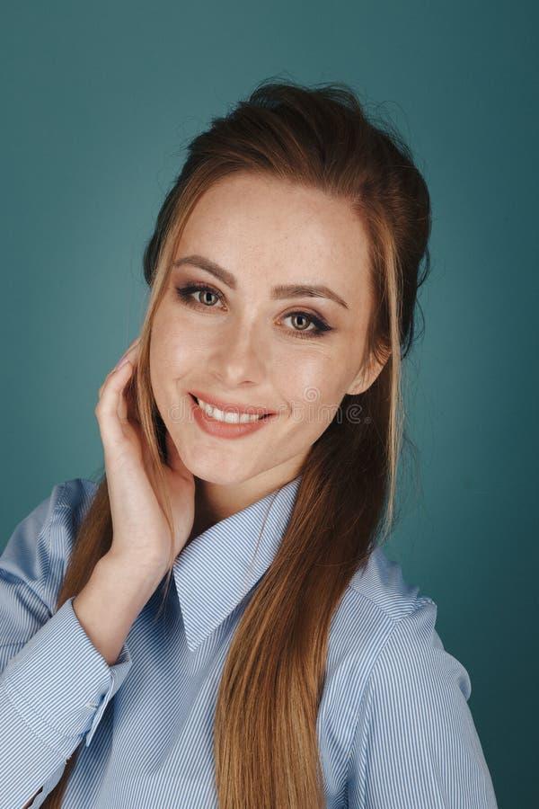 Портрет крупного плана милой женщины yong с ярким макияжем в студии изолированной над голубой предпосылкой стоковая фотография