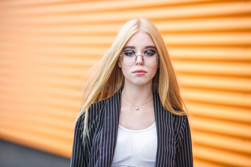 Портрет крупного плана милой усмехаясь маленькой модельной девушки в striped куртке и солнечных очках представляя около серого ри стоковые изображения