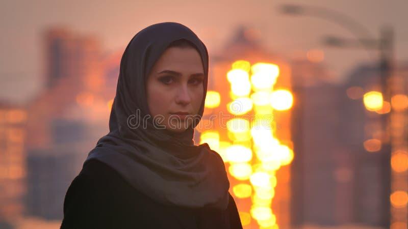 Портрет крупного плана молодой привлекательной мусульманской женщины в hijab поворачивая и смотря камеру со светя зданиями на стоковое изображение rf
