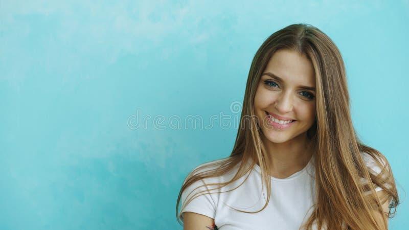 Портрет крупного плана молодой усмехаясь и смеясь над женщины смотря в камеру на голубой предпосылке стоковые изображения rf