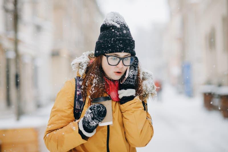 Портрет крупного плана на открытом воздухе милого счастливого кавказского девочка-подростка с на вынос кофе говоря на смартфоне стоковое фото rf