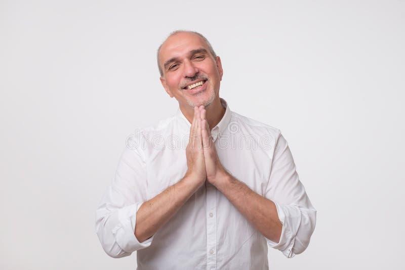 Портрет крупного плана отчаянного зрелого человека в белым руках рубашки сжиманных показом, просящ помощь или отговорка стоковая фотография rf