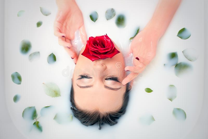 Портрет крупного плана очарования в ванне молока с и лепестках розы листьев стоковое фото