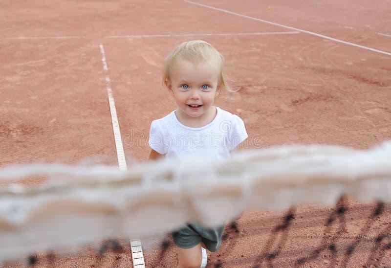 Портрет крупного плана смешной шаловливой маленькой девочки за сетью тенниса Портрет милого теннисиста младенца стоковое изображение