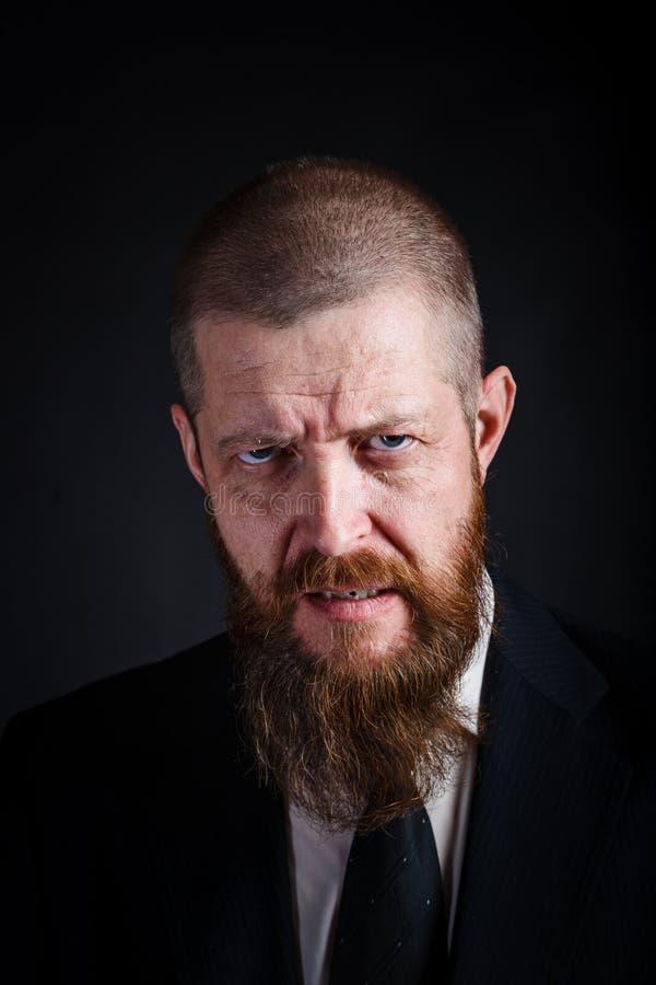Портрет крупного плана средн-достигшего возраста бородатого бизнесмена с сердитым взглядом на черной предпосылке стоковое фото