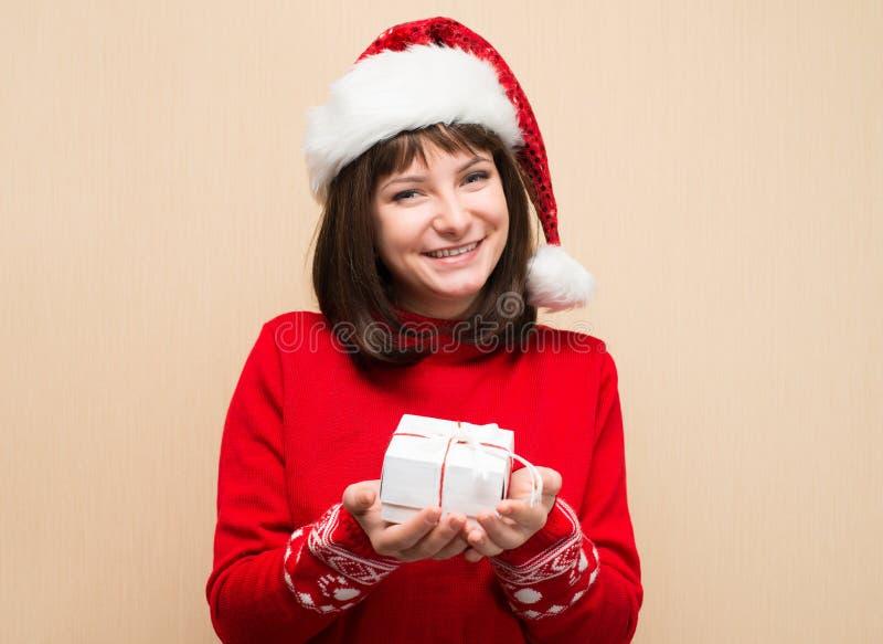 Портрет крупного плана девушки Санты держа подарок рождества Протокол доступа к хост-машине детенышей стоковые изображения
