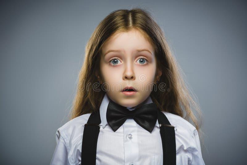Портрет крупного плана интересуя сюрприза девушки идя на серой предпосылке стоковая фотография
