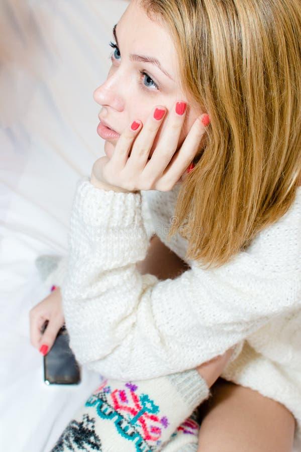 Портрет крупного плана красивой белокурой девушки голубых глазов молодой женщины в связанный смотреть заботливо на белой предпосы стоковое фото rf