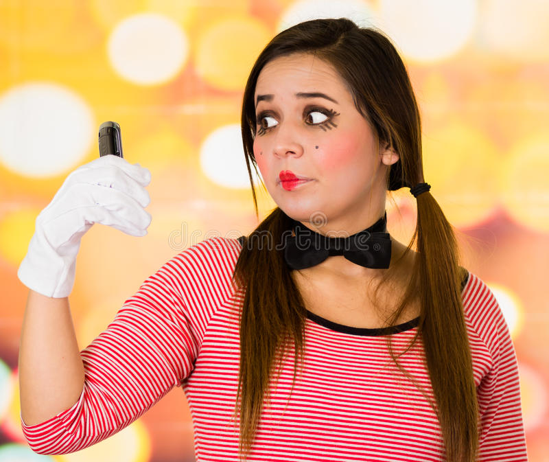 Портрет крупного плана милого телефона обнесенное решеткой места в суде пантомимы клоуна маленькой девочки стоковое фото