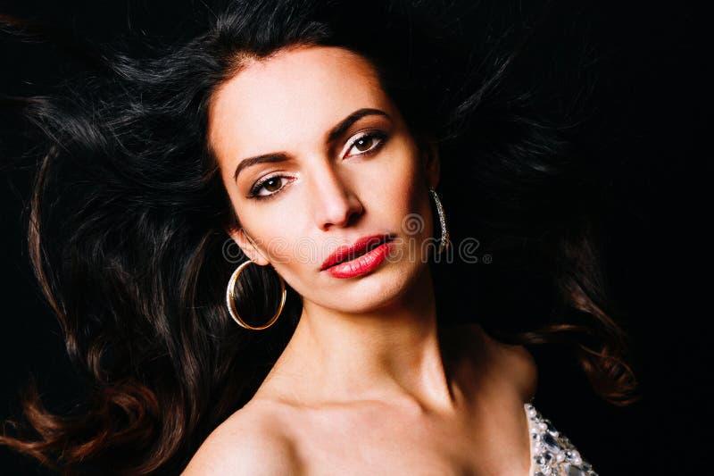 Портрет крупного плана молодой женщины брюнет при длинное вьющиеся волосы представляя на темной предпосылке, и взгляды на вас стоковые фотографии rf