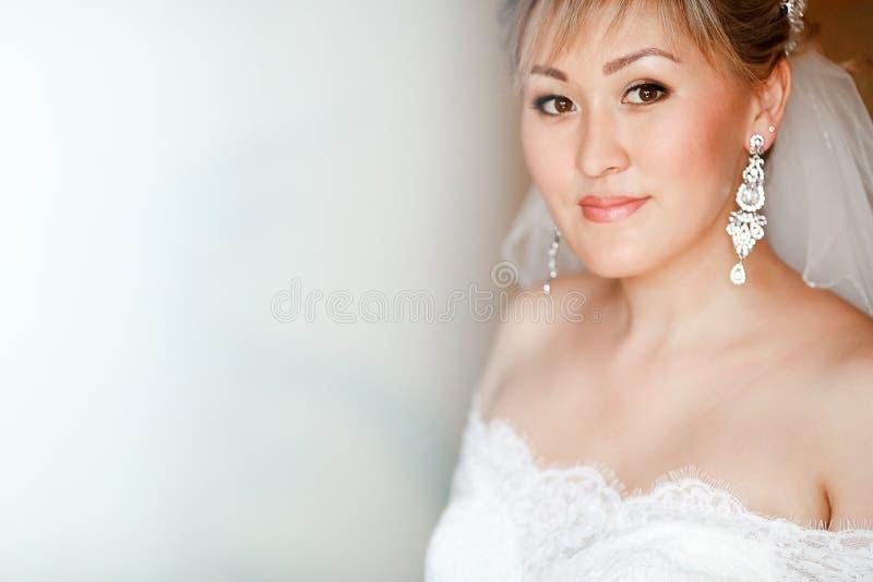 Портрет крупного плана невесты в платье свадьбы с элегантными серьгами, космосе шнурка белом экземпляра стоковая фотография