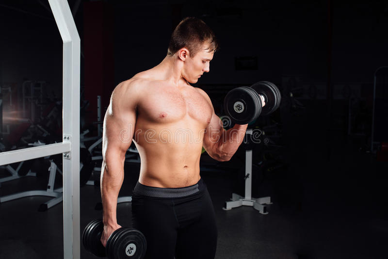 Портрет крупного плана человека yang профессионального культуриста сильного мышечного делая тренировку Разминка с штангой на спор стоковое фото