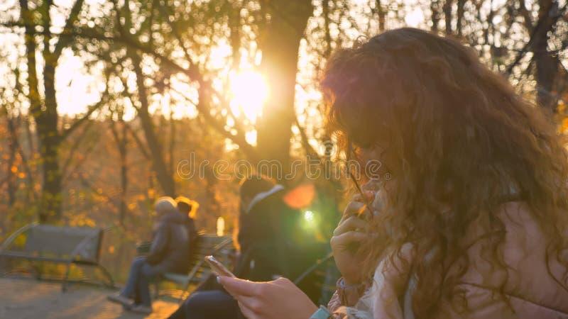 Портрет курчавой кавказской девушки сидя на стенде и наблюдая в смартфон с интересной улыбкой в осеннем стоковые изображения rf