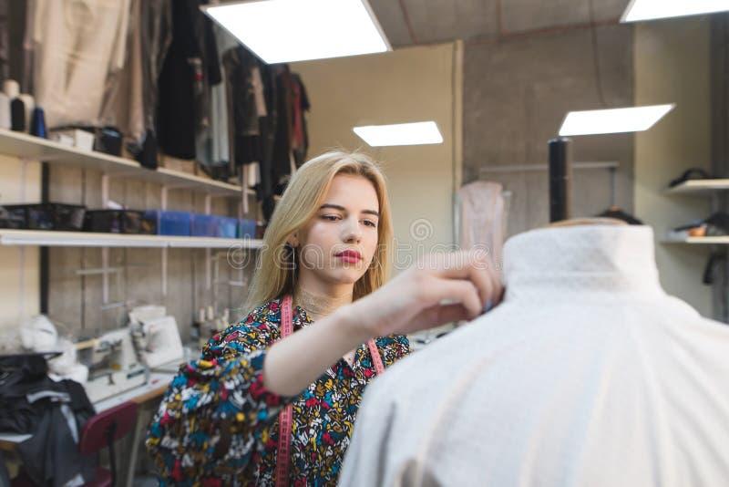 Портрет кутюрье девушки который создает одежды в ее собственной студии дизайна работа способа конструктора стоковая фотография